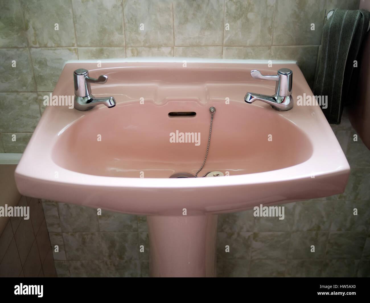 Rosa retrò il lavandino del bagno in bagno di colore verde foto