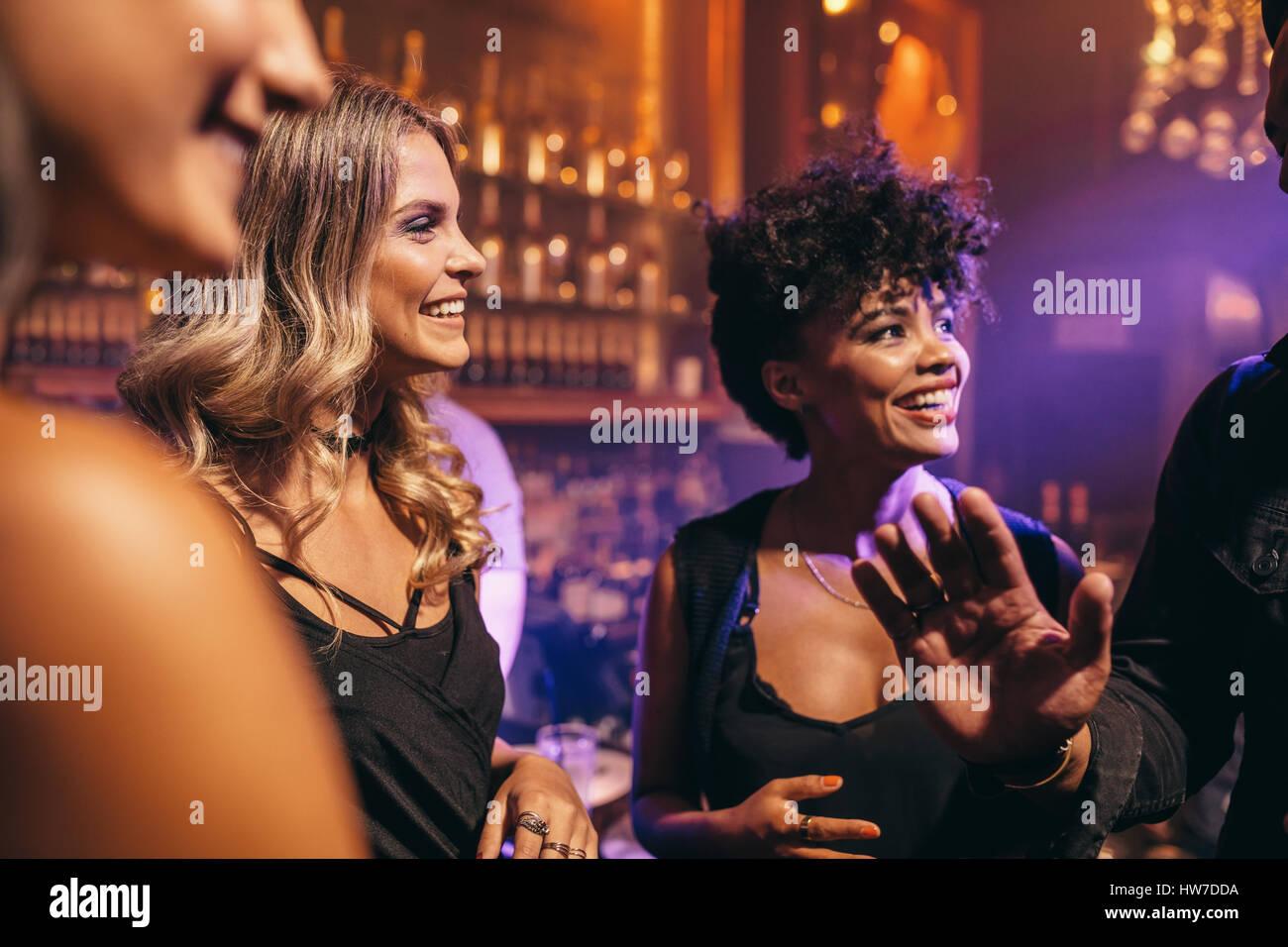 Un gruppo di giovani amici godendo di una notte al pub. Giovani divertendosi al night club. Foto Stock