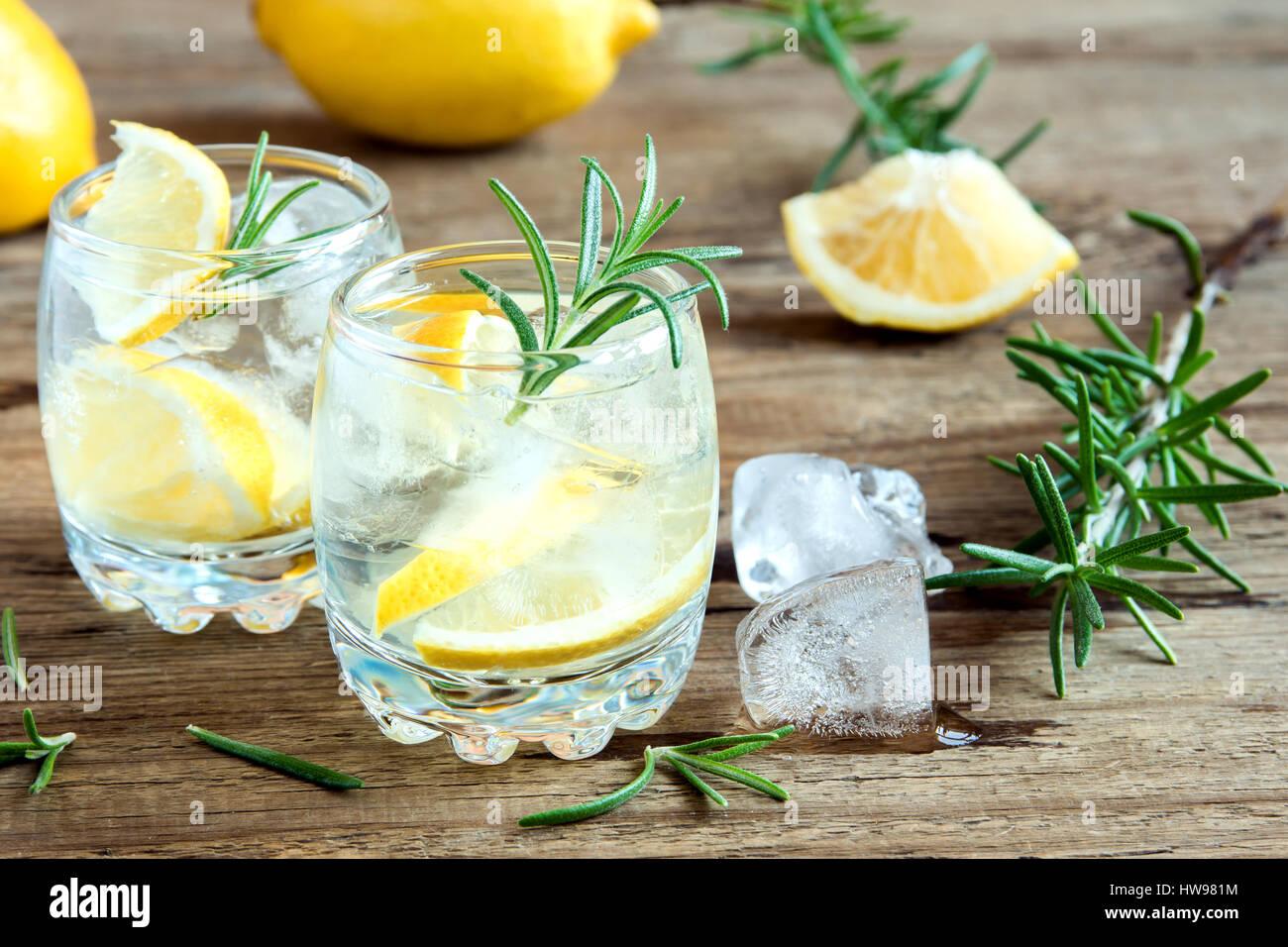 La bevanda alcolica (gin tonic cocktail) con limone e rosmarino e ghiaccio su tavola in legno rustico, spazio di Immagini Stock