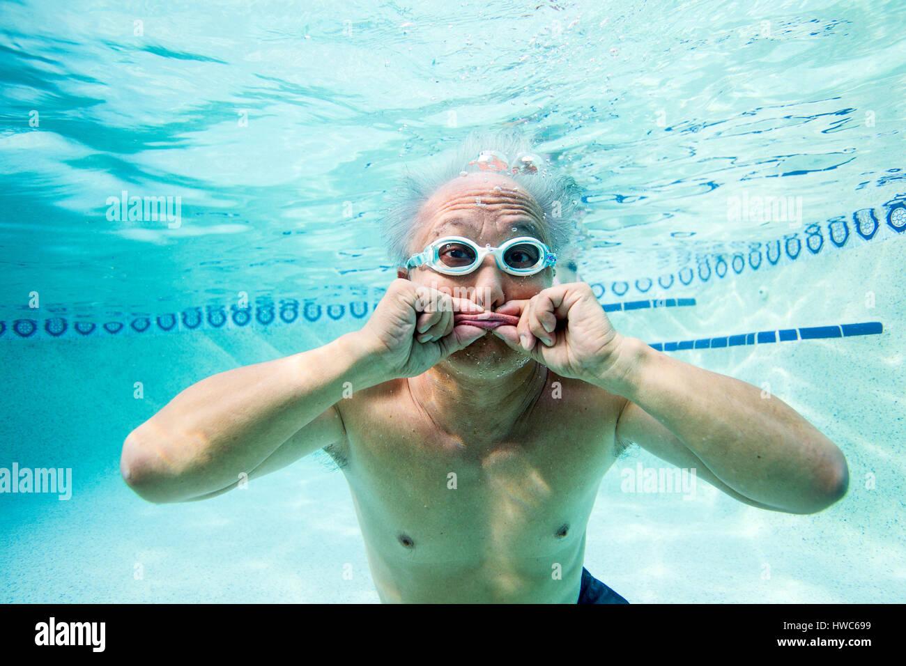 Senior essendo silly sott'acqua in una piscina Foto Stock