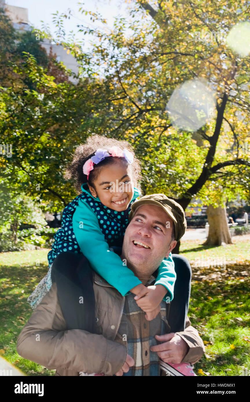 Padre dando sorridente figlia piggy back Immagini Stock