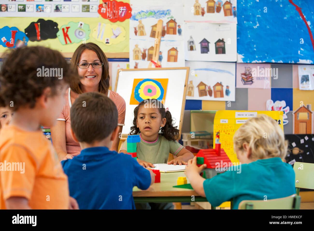 I ragazzi in età prescolare e ragazze edificio con blocchi giocattolo in aula Immagini Stock