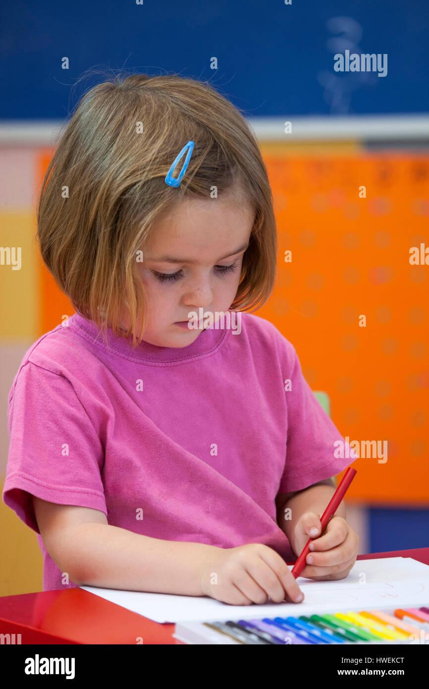 Ragazza in età prescolare con la colorazione di penna in aula Immagini Stock