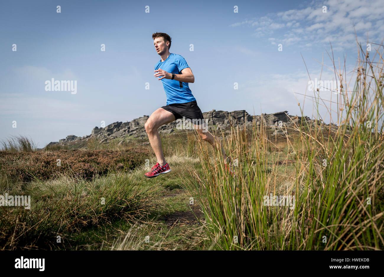 Maschio di runner acceso verso il basso dal bordo Stanage, Peak District, Derbyshire, Regno Unito Immagini Stock