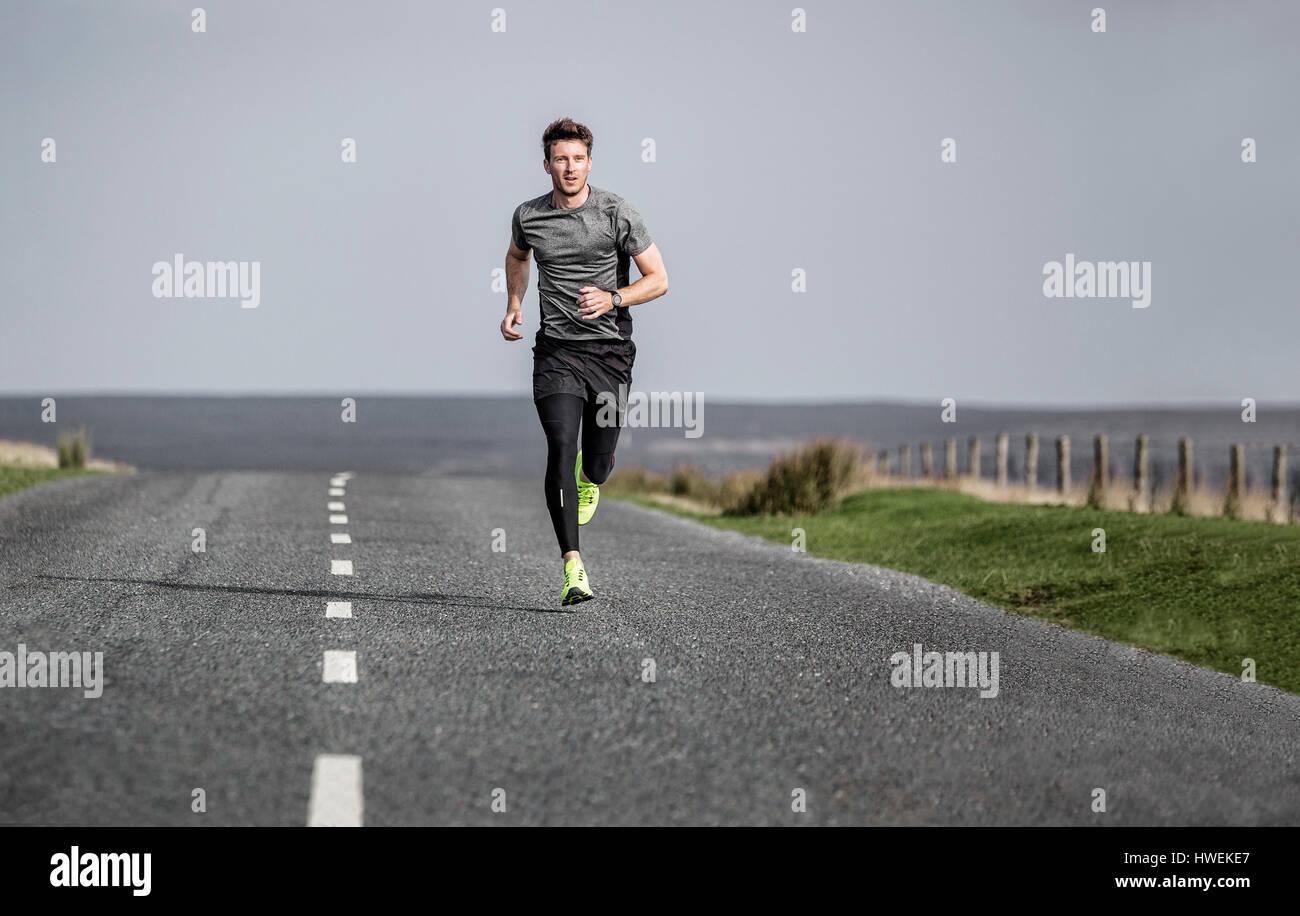 Maschio di runner che corre lungo la brughiera rurale road Immagini Stock