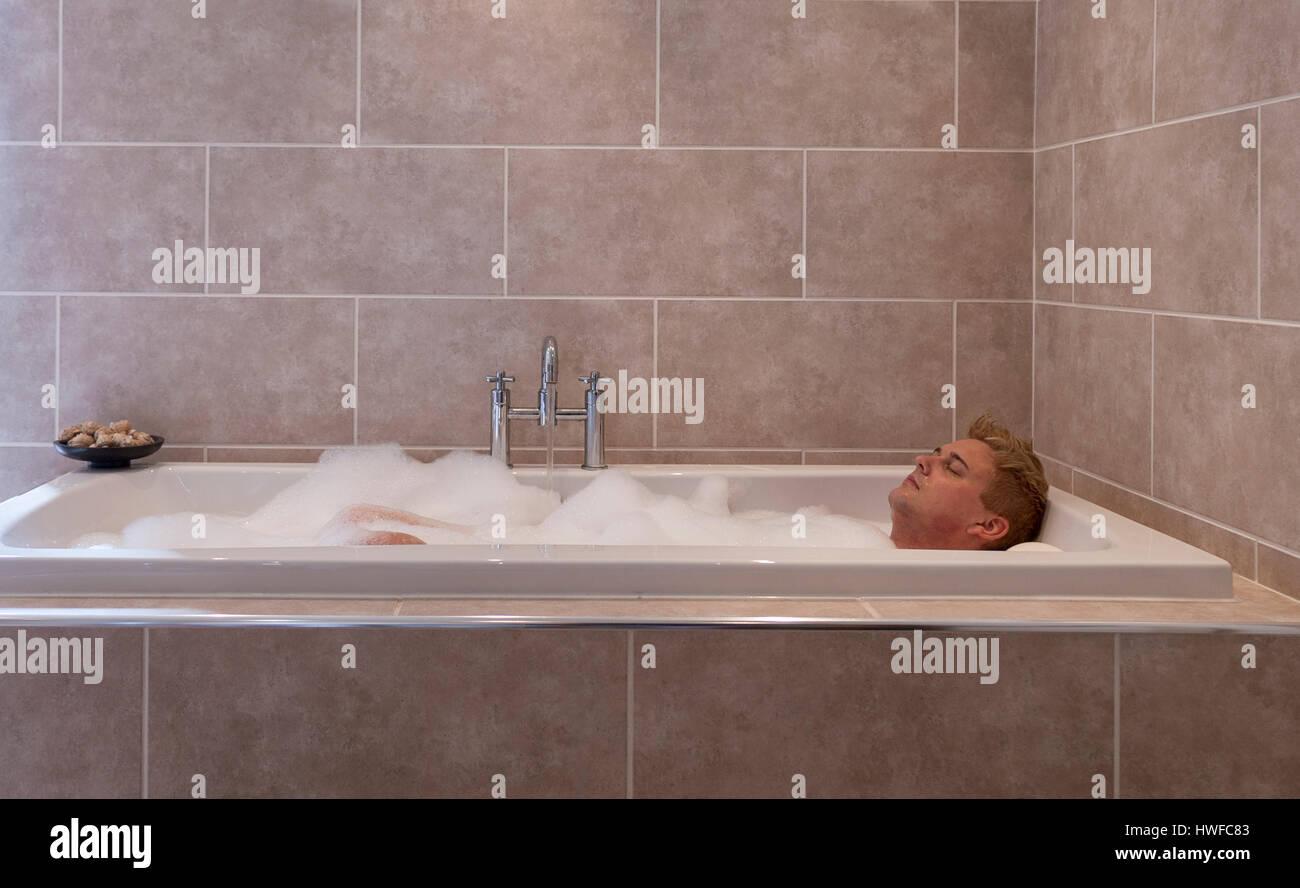Metà uomo adulto godersi un rilassante bagno di bolle in una