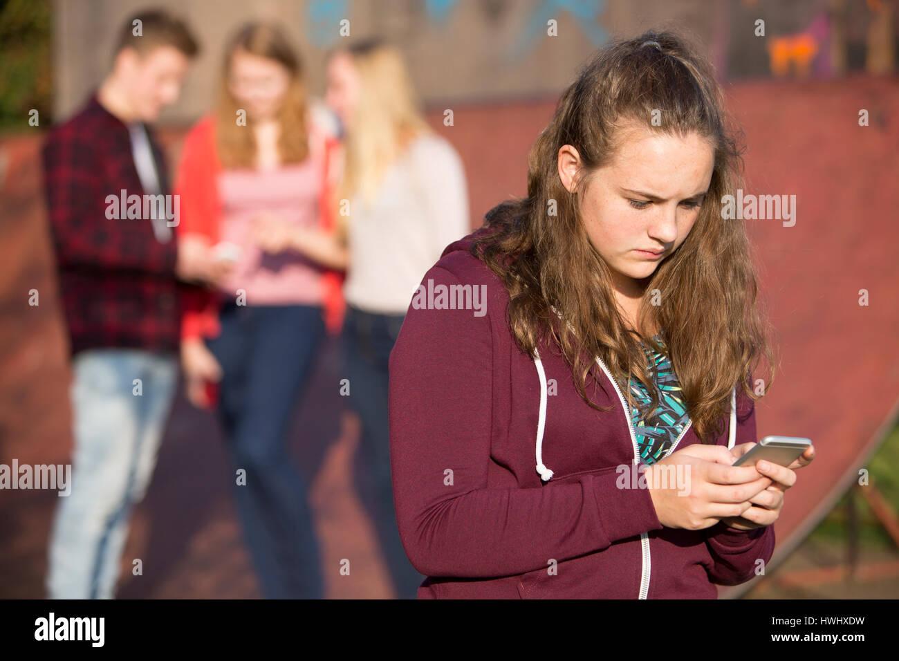 Ragazza adolescente vittima di bullismo mediante la messaggistica di testo Immagini Stock