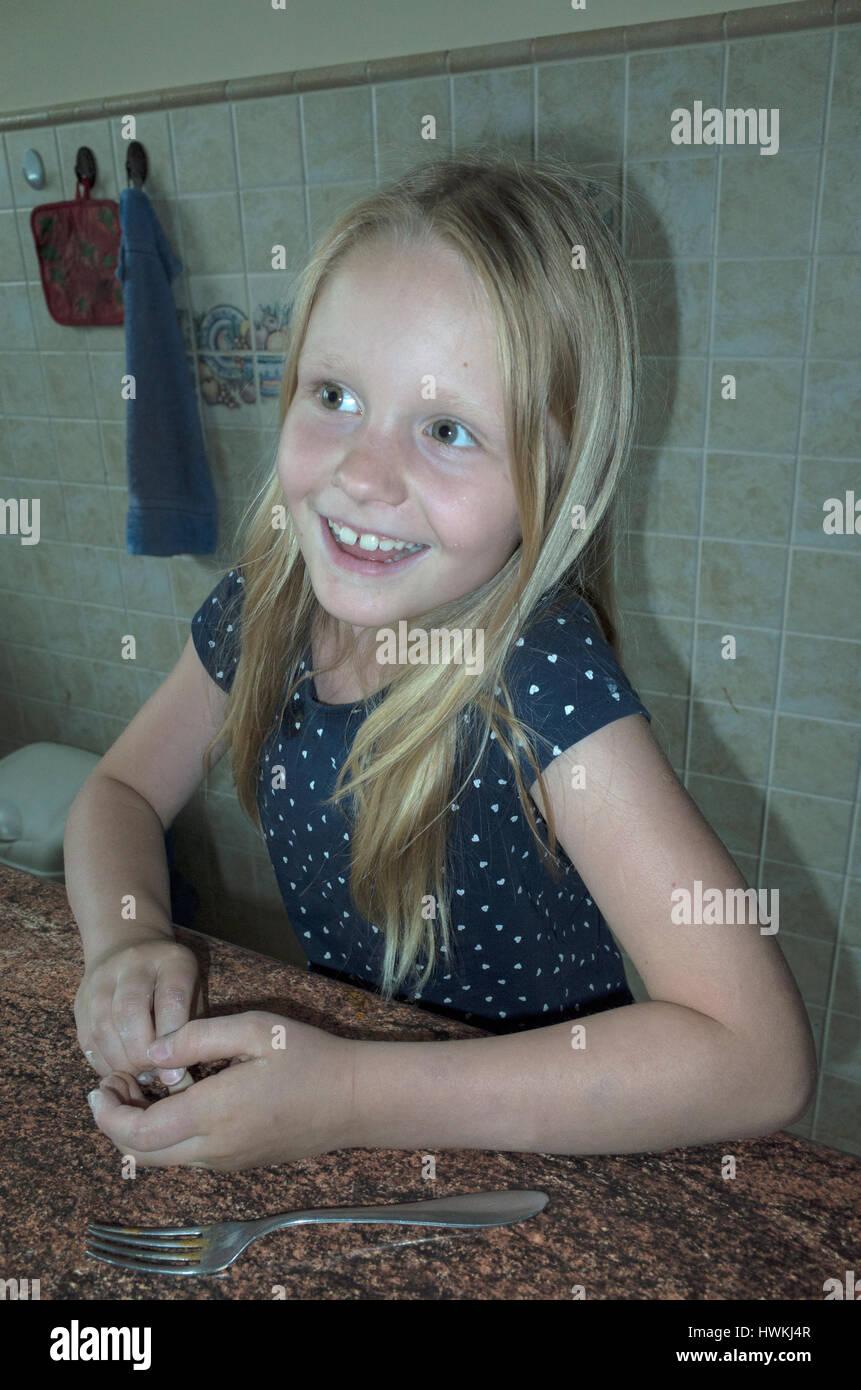 Ragazza giovane con un sorriso scintillanti in attesa al tavolo da cucina di età di 8. Zawady Polonia centrale Immagini Stock