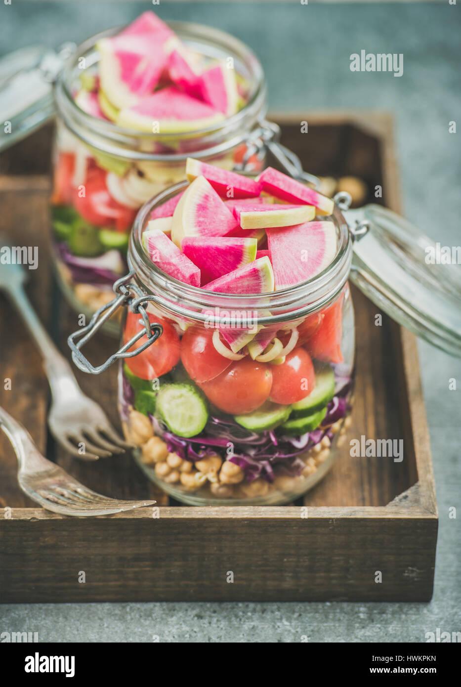 Close-up di sano take-away vasetti. Vegetali e germoglio di ceci vegan insalata in vasi di vetro nel vassoio di Immagini Stock