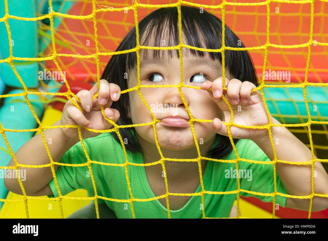 Felice cinese asiatici bambina giocando dietro la rete al parco giochi al coperto. Immagini Stock