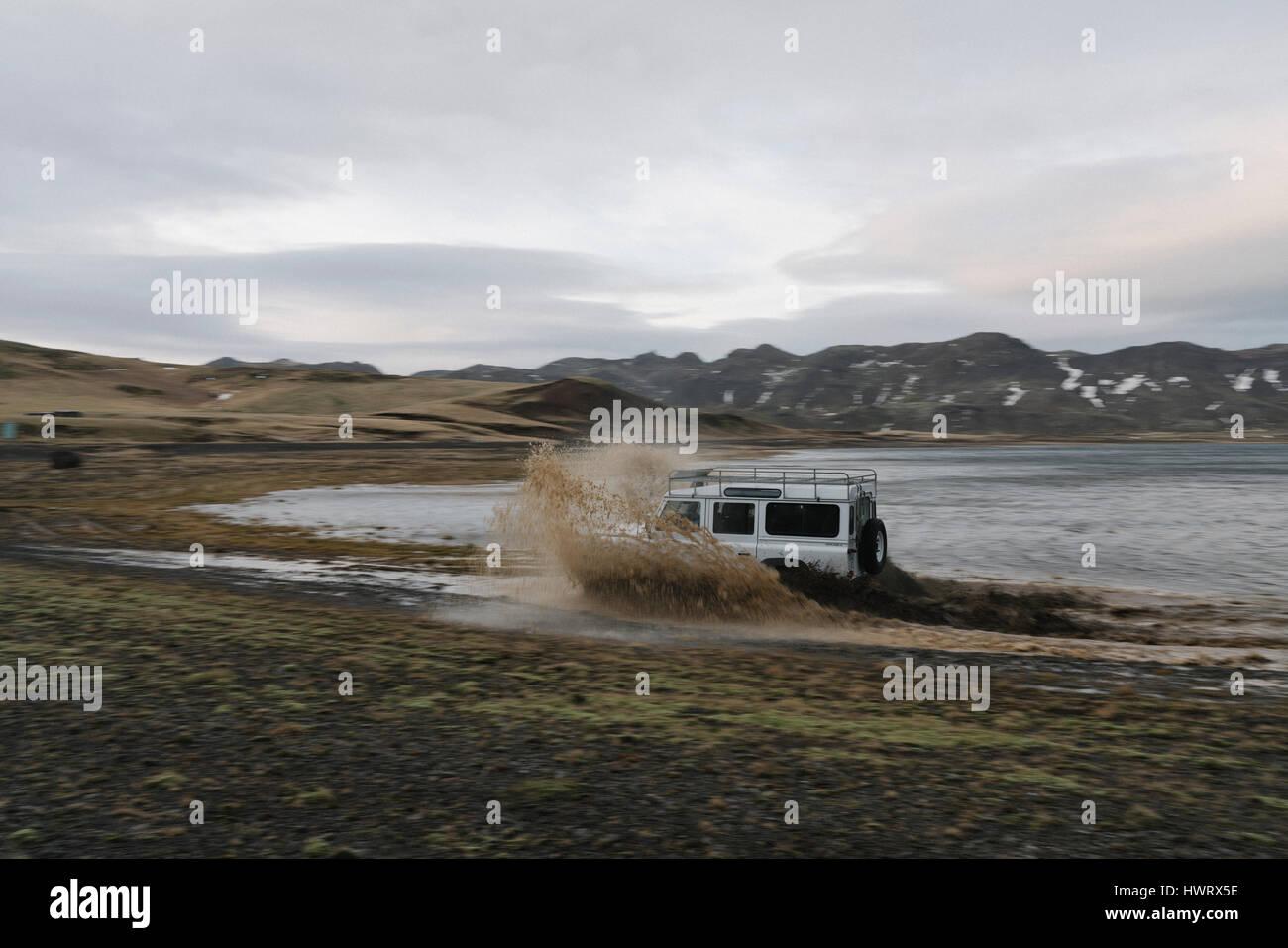 Land Rover guida fuori strada attraverso il robusto paesaggio islandese. Immagini Stock