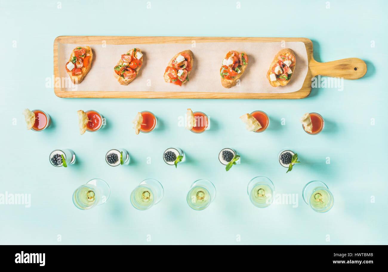 Spuntini, brushettas, gazpacho scatti, dessert, champagne pastello su sfondo blu Immagini Stock