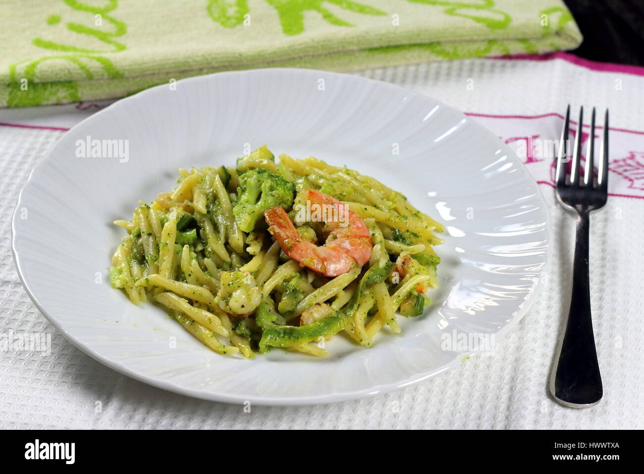 Le Trofie pasta con gamberi (gamberetti), broccoli, zucchini (zucchine) e pomodoro nel piatto bianco su bianco panno Immagini Stock