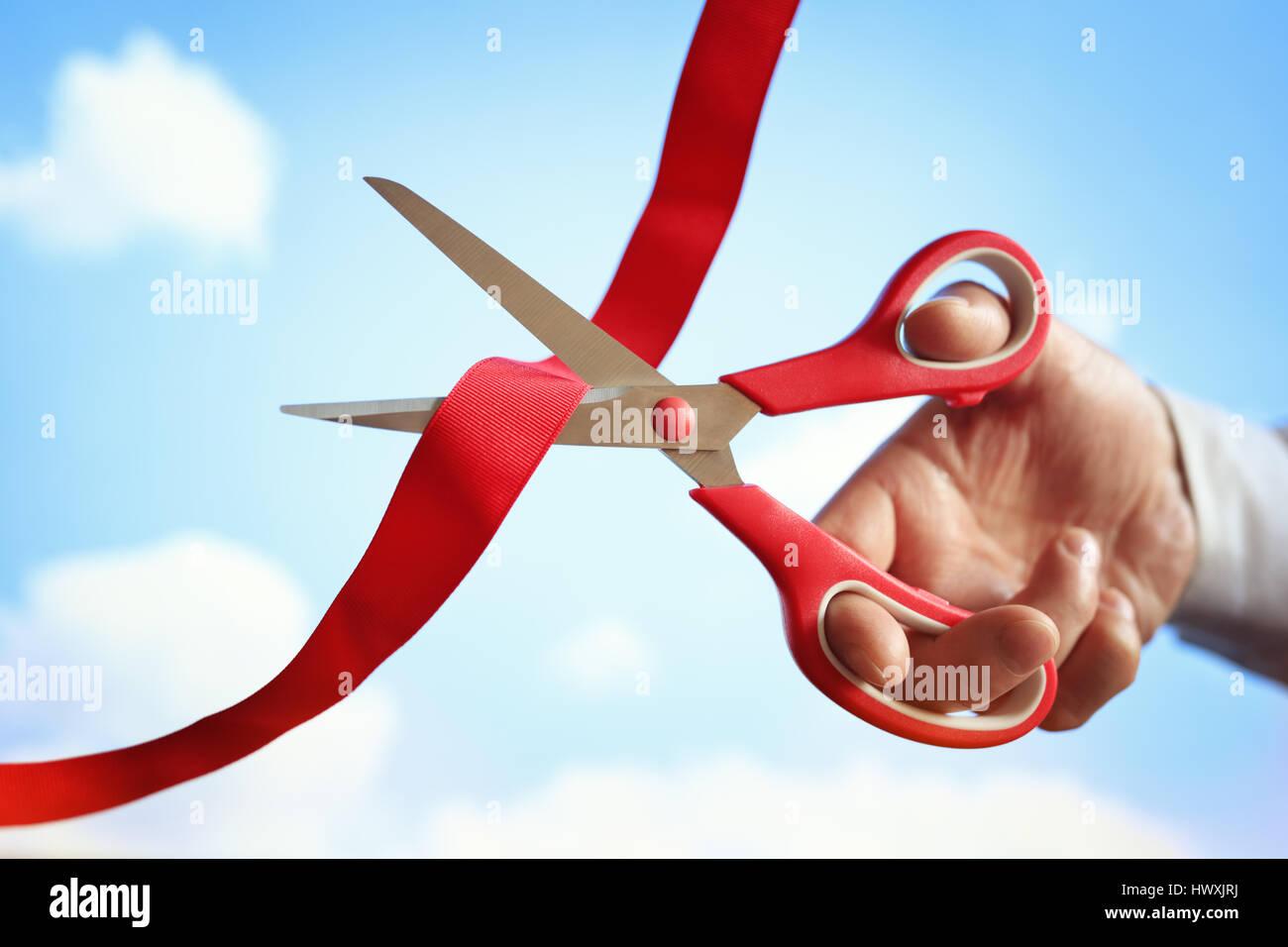 Imprenditore il taglio di un nastro rosso con un paio di forbici alla cerimonia di apertura Immagini Stock