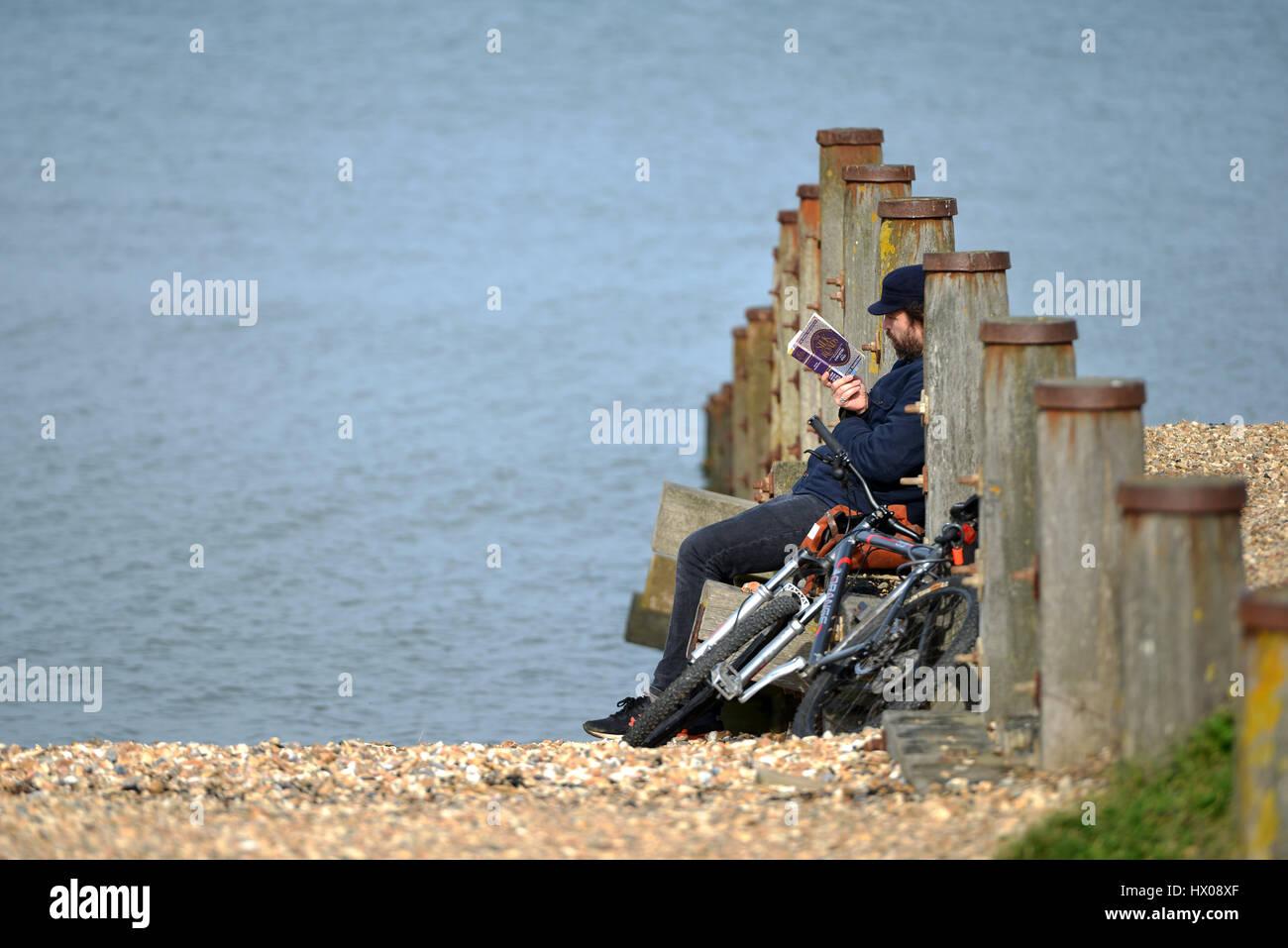 L'uomo con una moto che la lettura di un libro, Peter Frankopan di vie della seta, su una spiaggia di ciottoli, Immagini Stock