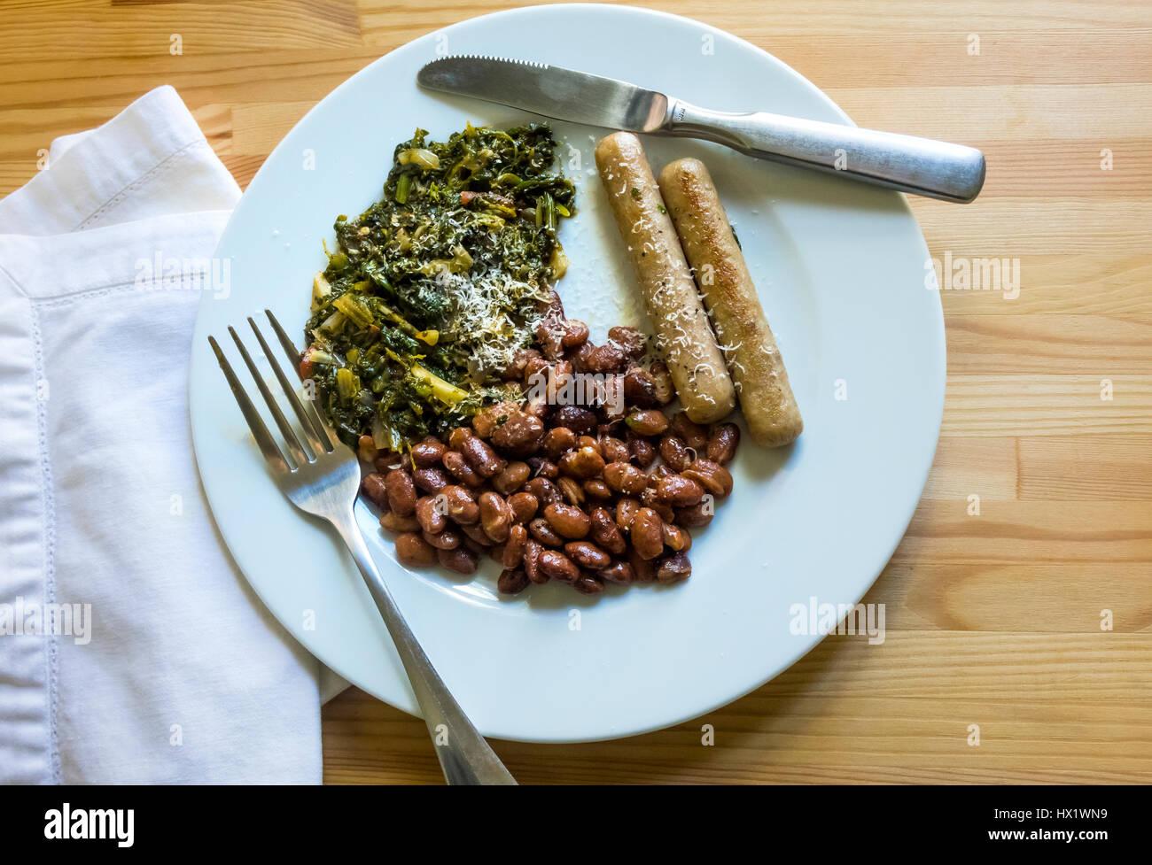 Salsicce e fagioli pinto, e gli spinaci con aglio Immagini Stock