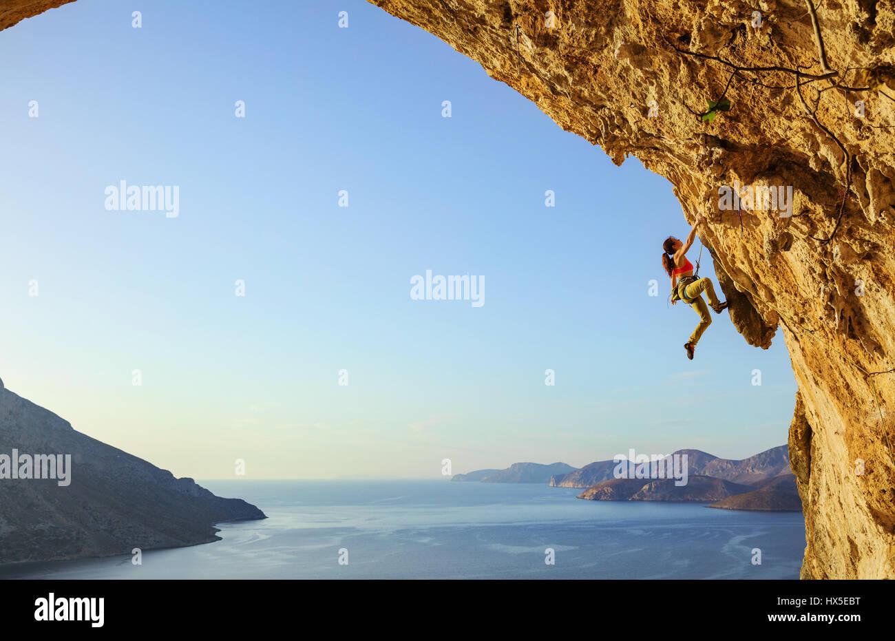 Giovane donna di arrampicata percorso impegnativo in grotta al tramonto, Kalymnos Island, Grecia Immagini Stock