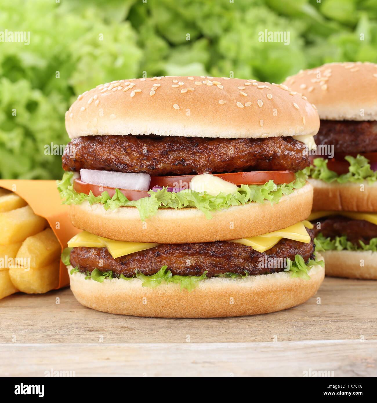 Double burger hamburger e patatine fritte pomodori lattuga fast food Immagini Stock