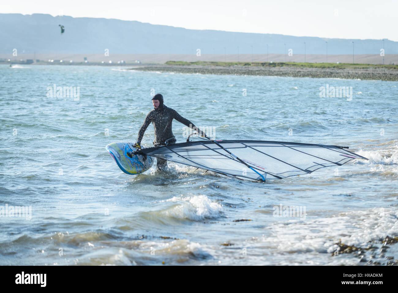 Portland Harbour, Dorset, Regno Unito. Il 26 marzo 2017. Un uomo prepara il suo wind surf di bordo su un croccante Immagini Stock