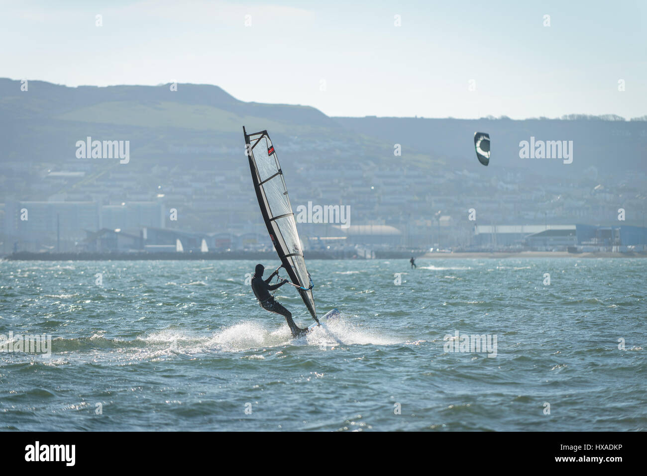Portland Harbour, Dorset, Regno Unito. Il 26 marzo 2017. Un uomo wind surf su un croccante di Ventoso giornata soleggiata Immagini Stock