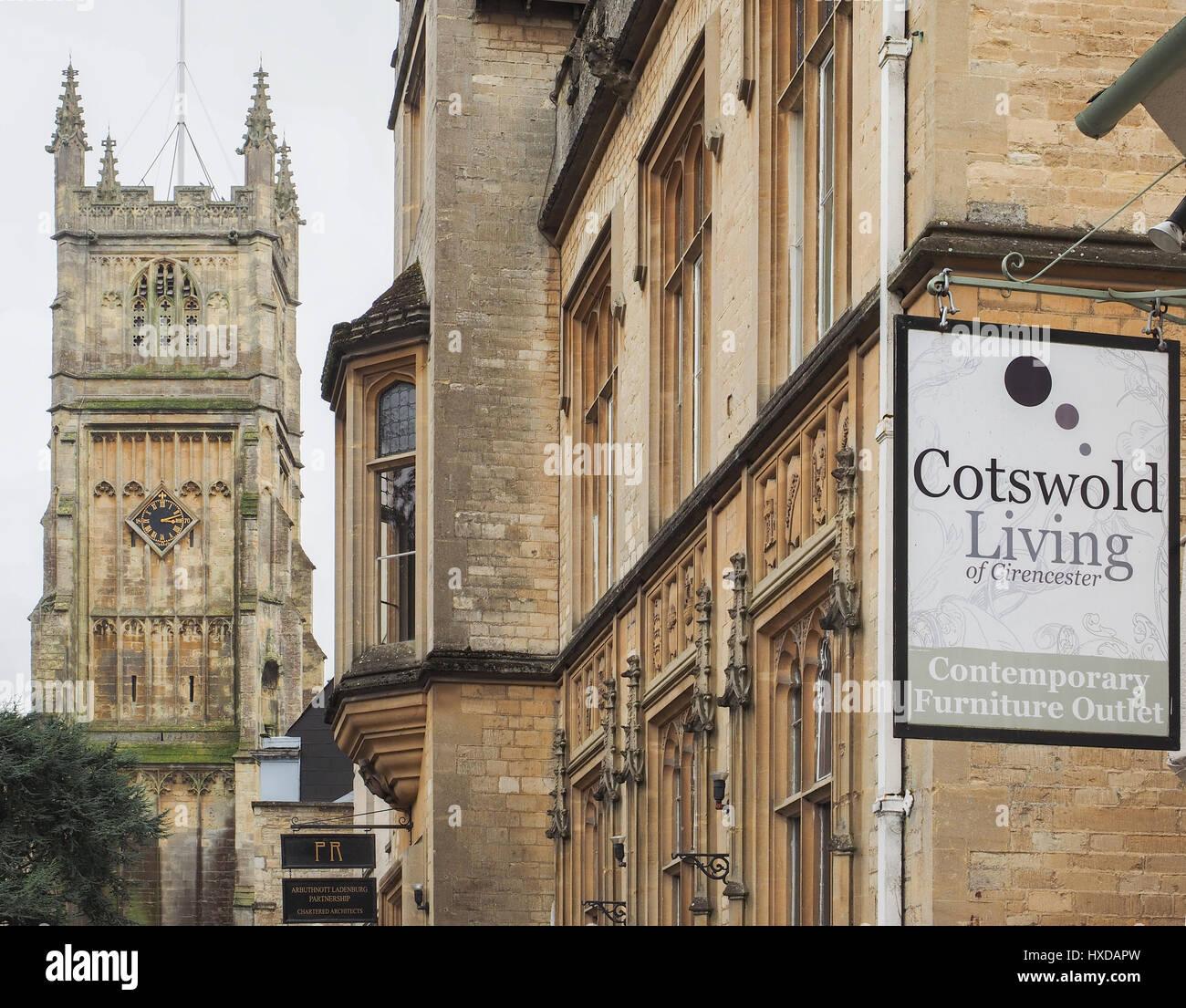 Un serrato colpo di architettura in Cirencester con San Giovanni Battista e Cotswold vivere appesi shop segno in Immagini Stock