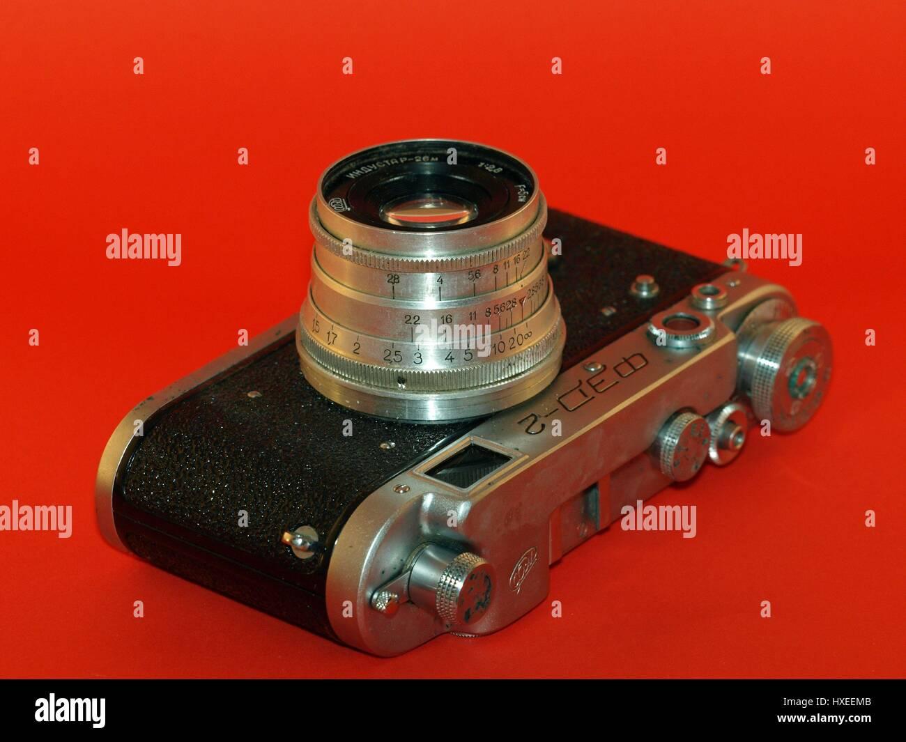 Antica telecamera con custodia in pelle su sfondo rosso Immagini Stock