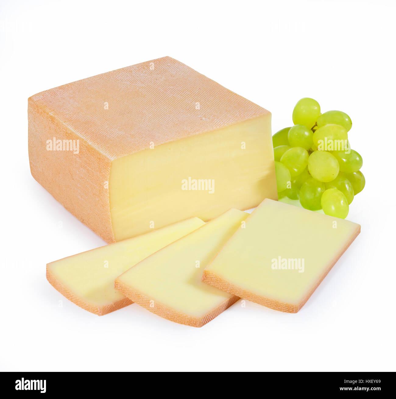 Formaggio, parzialmente tagliata a fette di formaggio raclette, uva (Vitis vinifera) come decorazione Immagini Stock