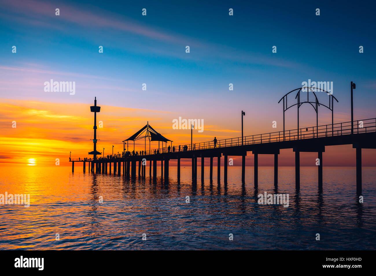 La gente camminare lungo il molo di Brighton al tramonto. Australia Meridionale Immagini Stock
