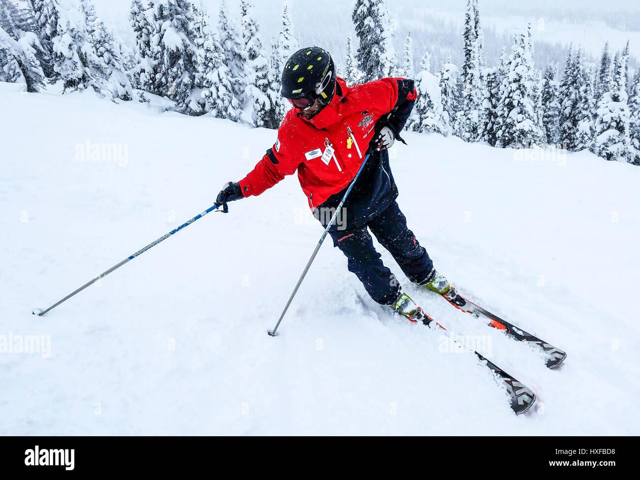 Durante la nevicata moderata che granuli il paesaggio, un istruttore a Big White ski resort mostra un esagerato Immagini Stock