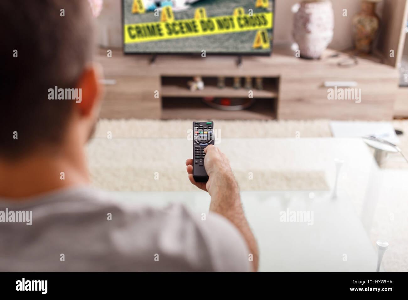 Uomo con telecomando a guardare la criminalità in serie TV di casa Immagini Stock