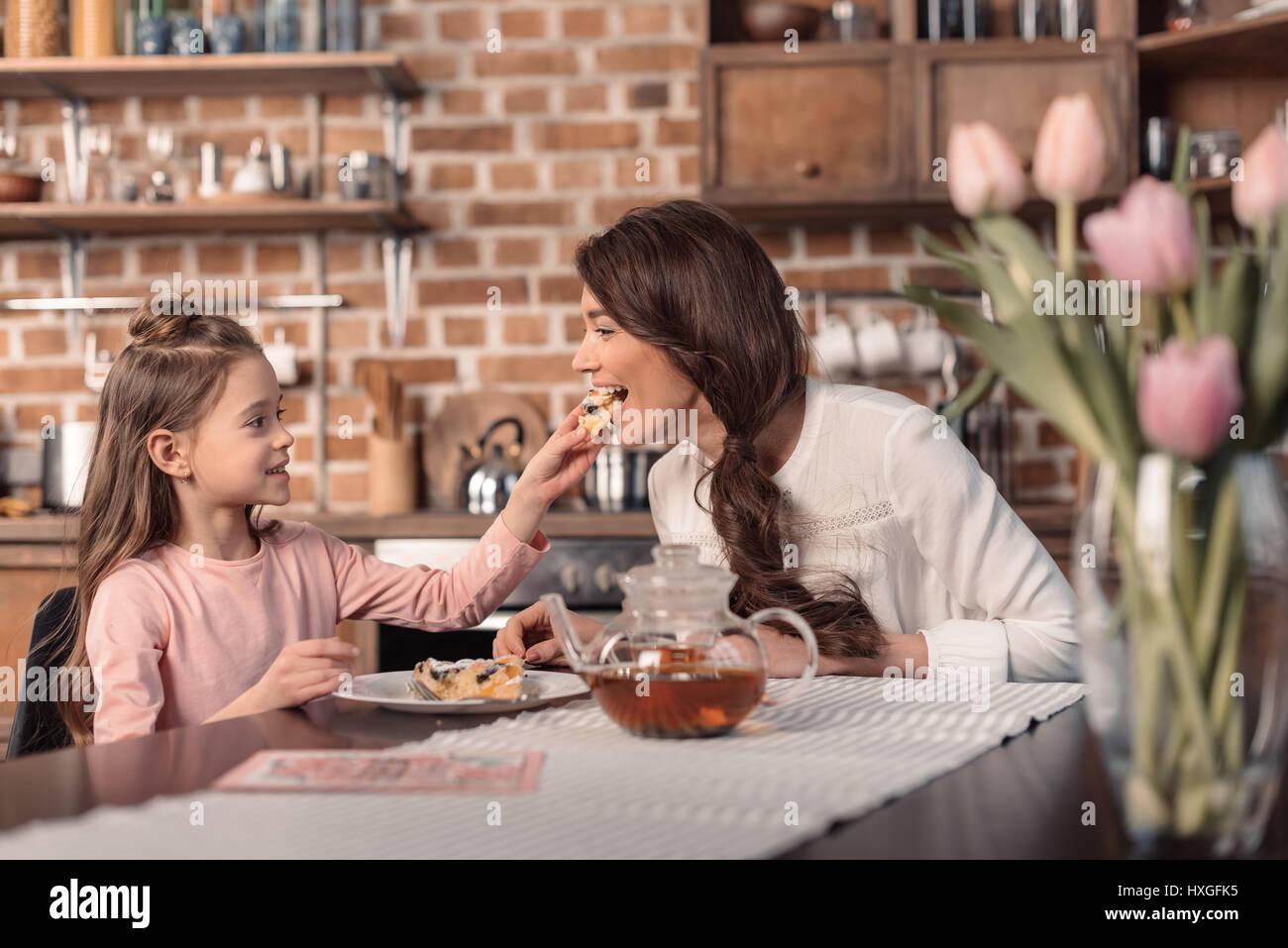 'Side View della figlia di madre di alimentazione con torta per la festa della mamma vacanze in cucina Immagini Stock