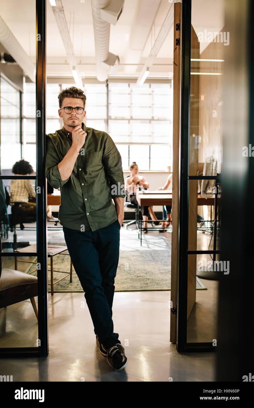 A piena lunghezza ritratto del bel giovane uomo in piedi nella porta di office con la gente che lavora in background. Immagini Stock