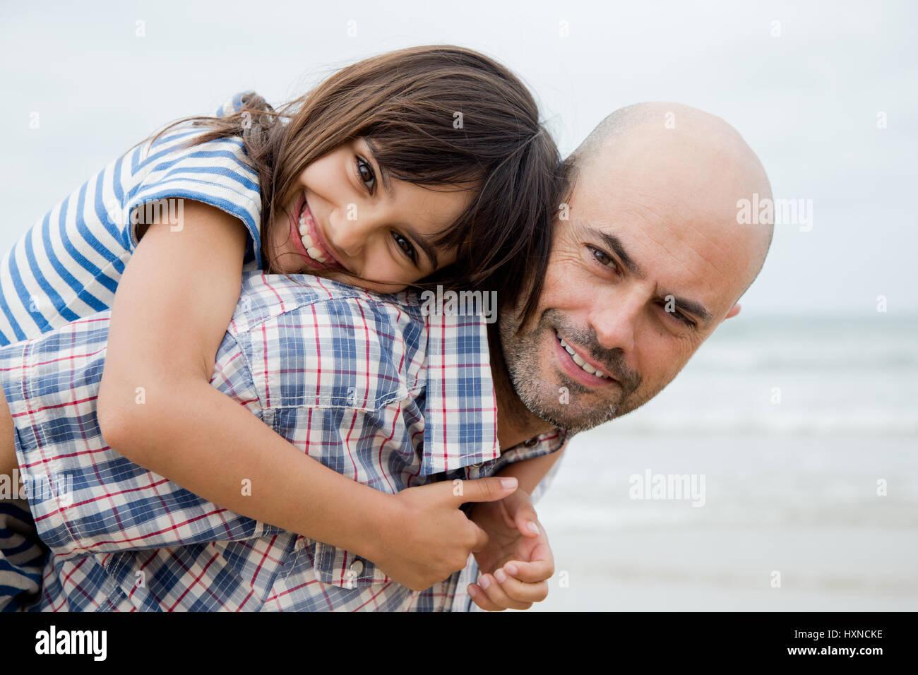 Padre dando la sua figlia una piggy back corsa sulla spiaggia in una giornata nuvolosa Immagini Stock
