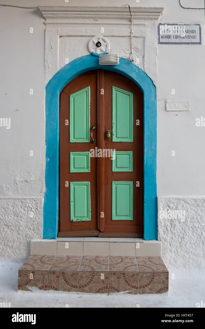 Hölzerne Eingangstüre hellgrün und braun mit türkiser Einfassung in weißer Fassade, Insel Immagini Stock