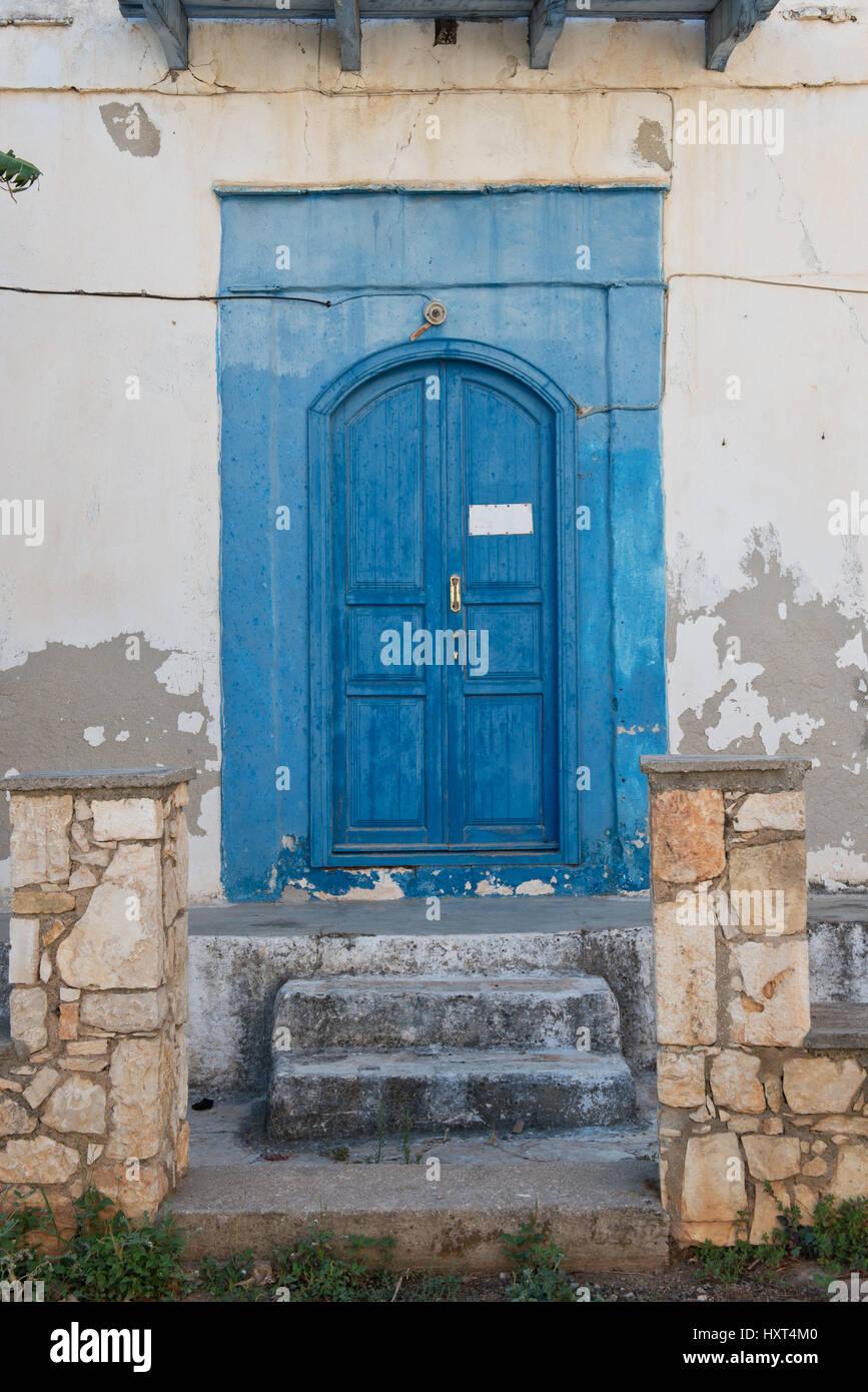 Alte blaugestrichene hölzerne Eingangstüre mit Stufen und blauer Einfassung in weißem Haus, Insel Immagini Stock
