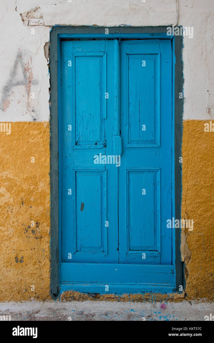 Eine alte Eingangstüre aus Holz, blau gestrichen in gelber Hauswand, Insel Kastellorizo, Dodekanes, Griechenland Immagini Stock