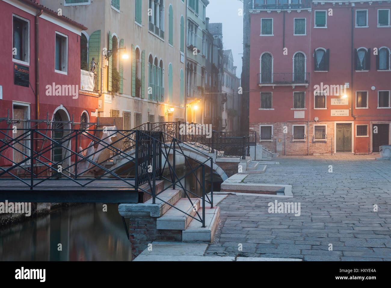 Mattinata nebbiosa su un canale nel sestiere di San Marco, Venezia, Italia. Immagini Stock
