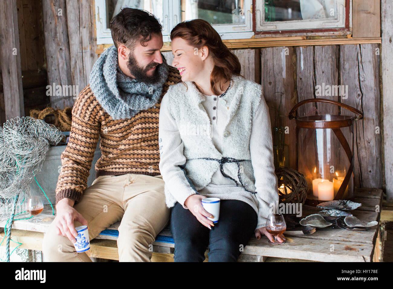 La Svezia, coppia giovane seduto su un tavolo di legno e parlare Immagini Stock