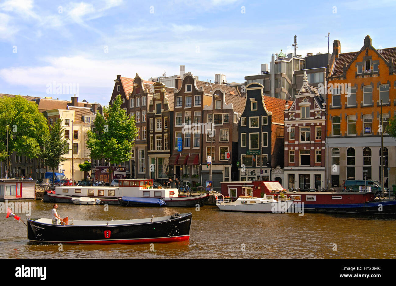 Immagine della piccola imbarcazione a motore di guida in un canale di acqua nella parte interna della città di Amsterdam, Olanda. Foto Stock