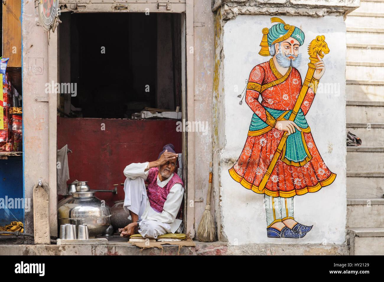 Chai wallah nella sua stalla accanto a un Rajput pittura murale in Udaipur Immagini Stock