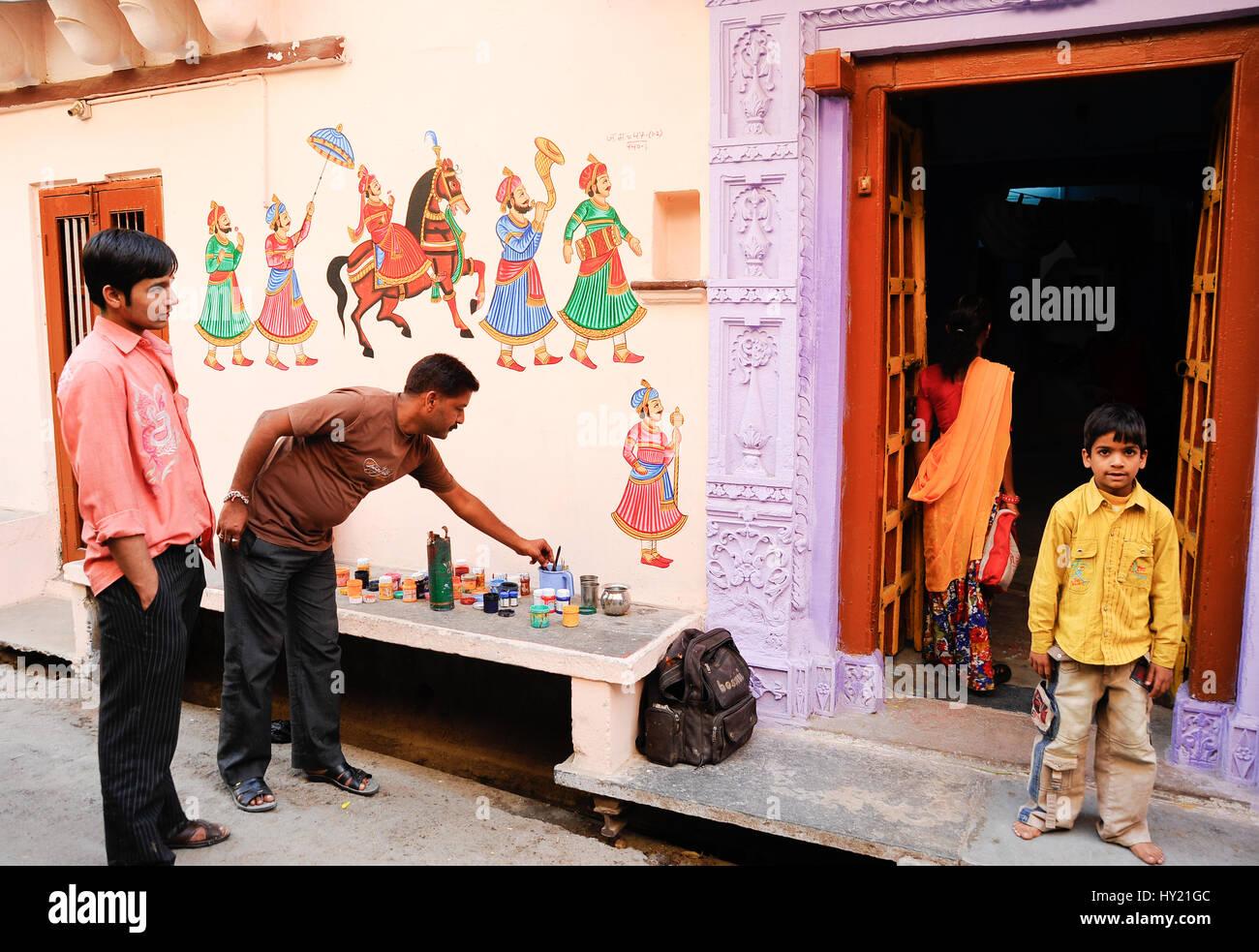 Un uomo pittura Rajput tradizionali disegni su una casa per celebrare un matrimonio, Udaipur Città Immagini Stock