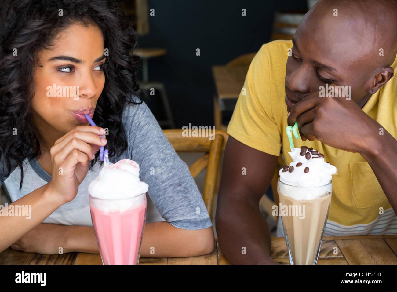 Amorevole coppia giovane avente frappè al tavolo in coffee shop Immagini Stock