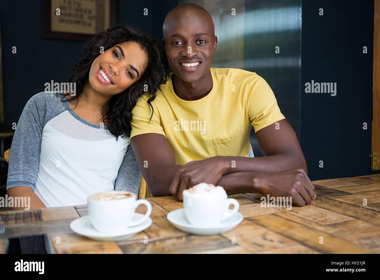 Ritratto di felice amare giovane seduto a tavola in un coffee shop Immagini Stock