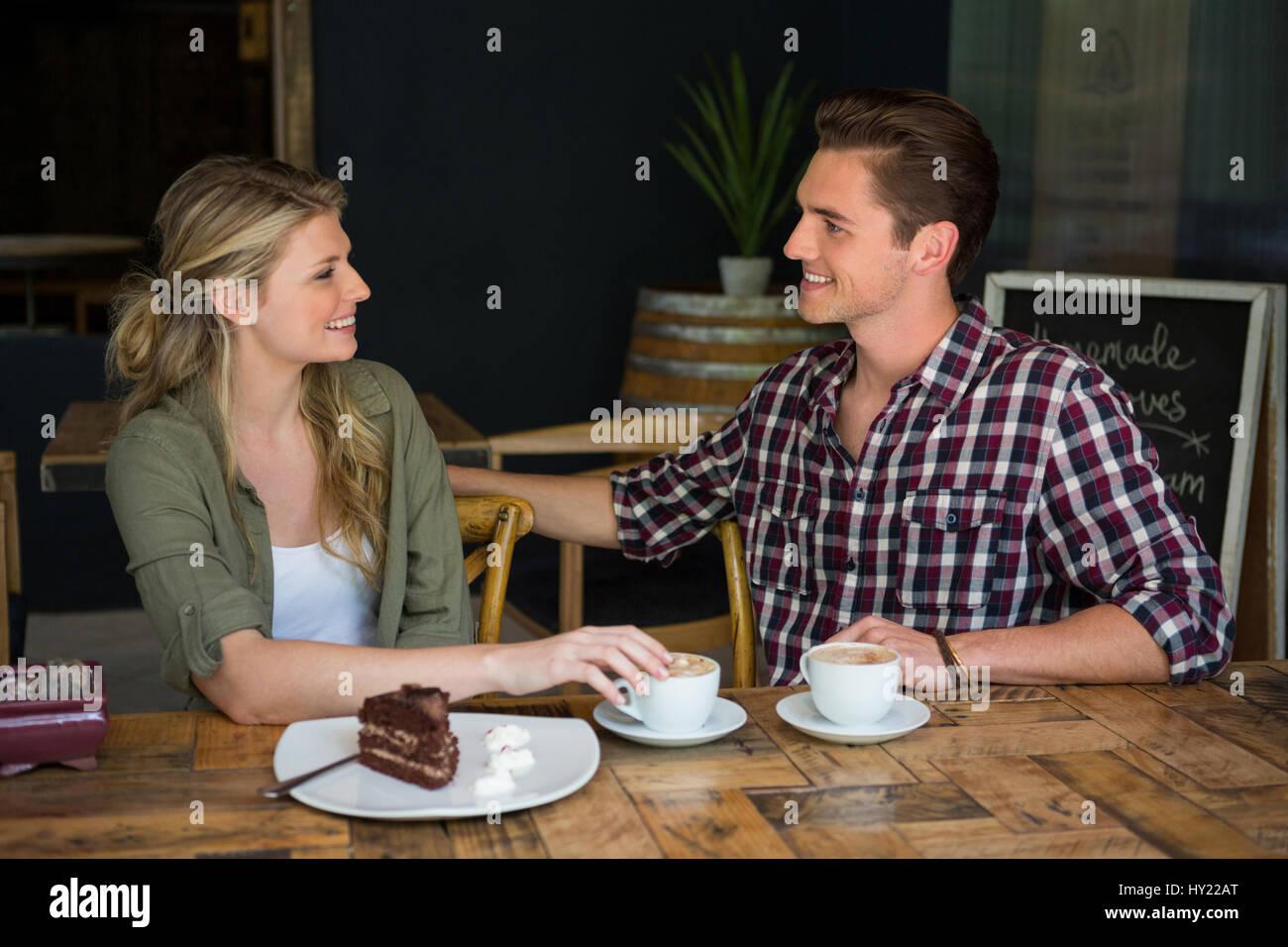 Amorevole coppia giovane parlando a tavola in coffee shop Immagini Stock