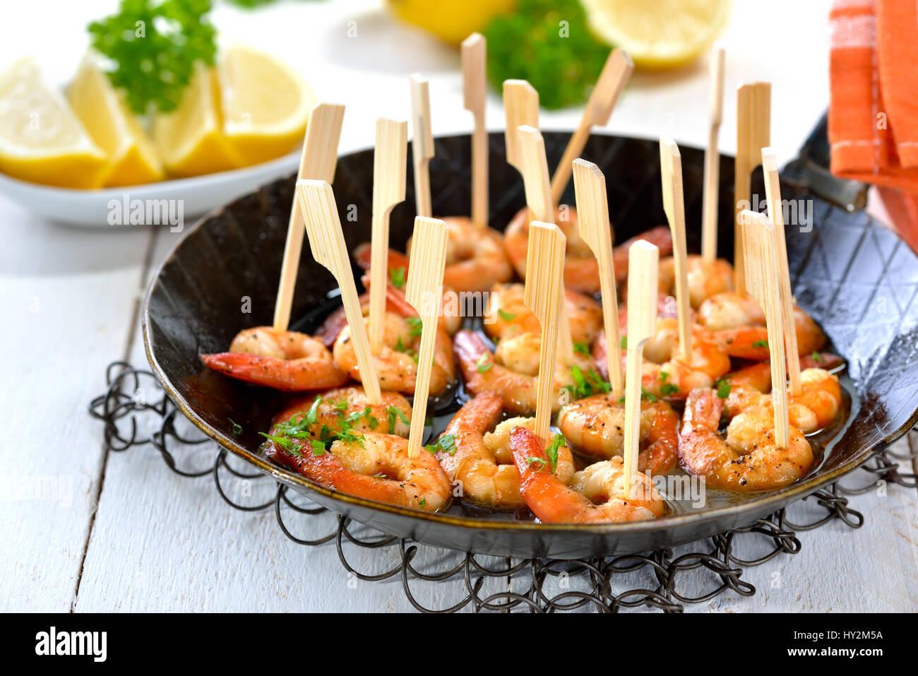Tapas spagnoli - piccante fritto di gamberi con olio d'oliva, Sherry e aglio, servita in un ferro da stiro padella Immagini Stock