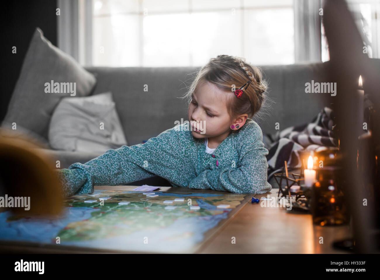 La Svezia, ragazza (4-5) riproduzione del gioco di bordo sul tavolino da caffè Immagini Stock