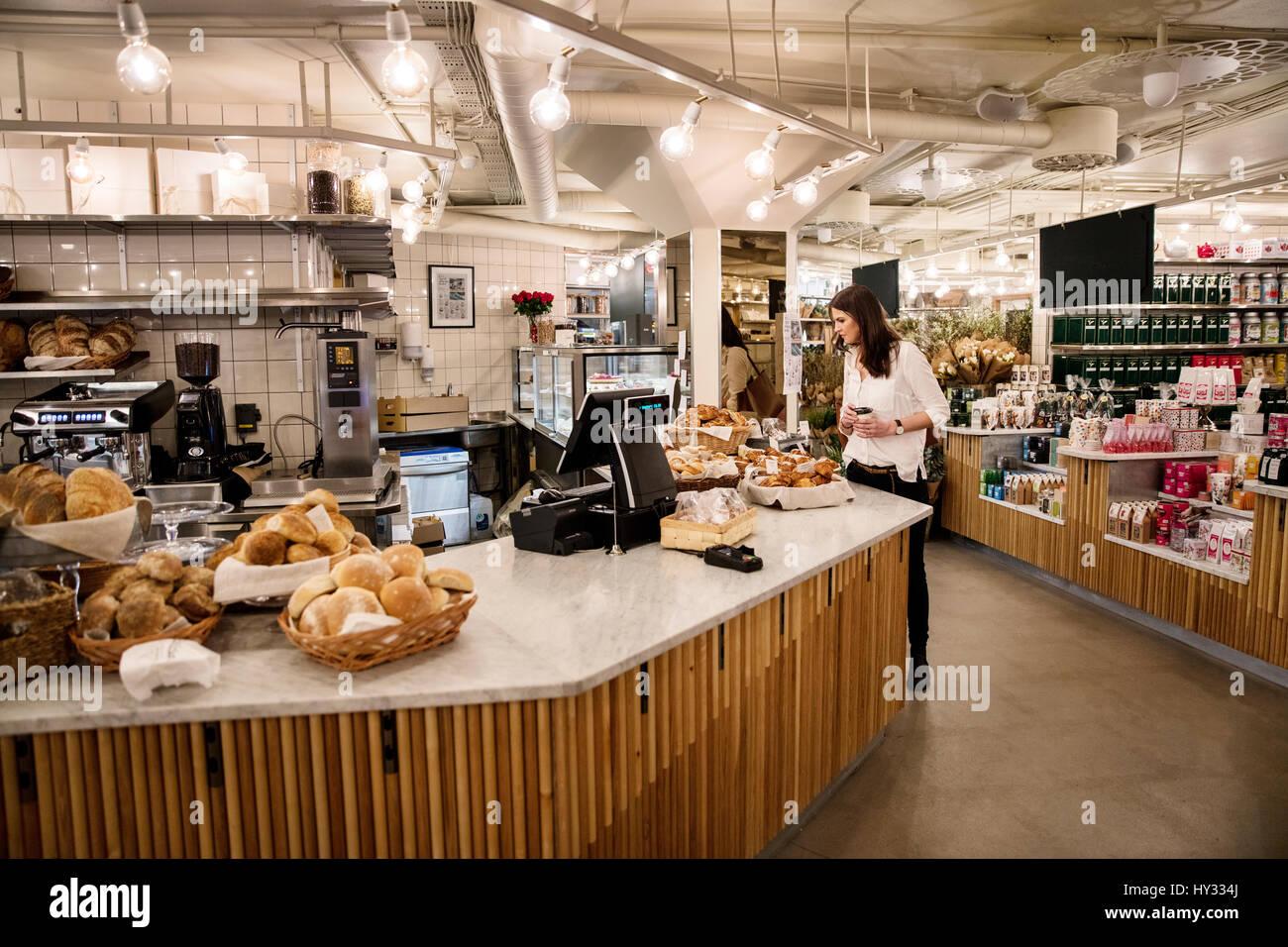 La Svezia, Donna scelta dei cibi in forno Immagini Stock