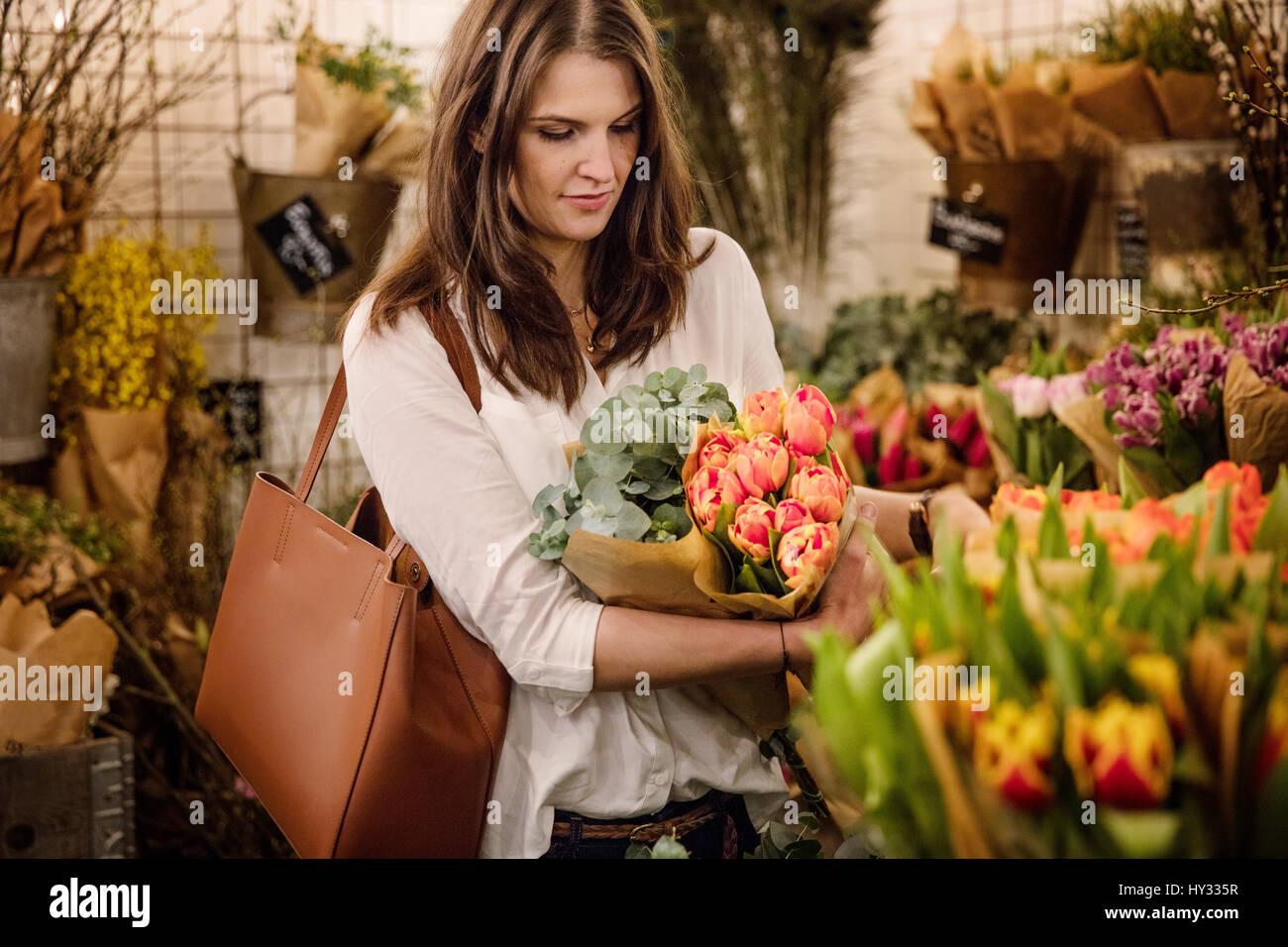 La Svezia, Donna scelta di fiori in negozio Immagini Stock