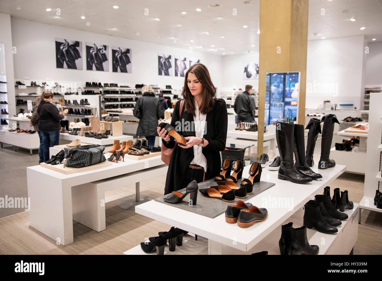 La Svezia, Donna scelta di scarpe in negozio Immagini Stock