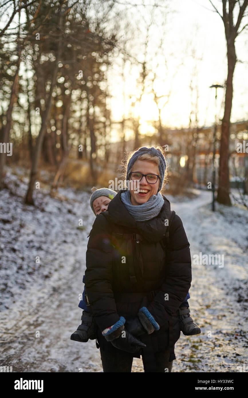 La Svezia sodermanland, Stoccolma johanneshov, hammarbyhojden, ridendo metà donna adulta che trasportano figlio Immagini Stock